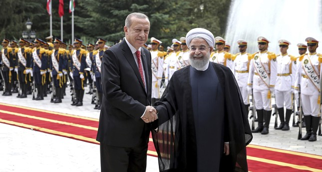 Erdoğan (L) shakes hands for the cameras with Iranian President Rouhani, during the official arrival ceremony, at the Saadabad Palace in Tehran Oct. 4, 2017. (AP Photo)