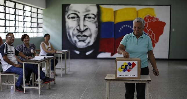 Electoral officials watch as a woman casts her vote at a polling station during the Constituent Assembly election in Caracas, Venezuela, July 30, 2017. (Reuters Photo)