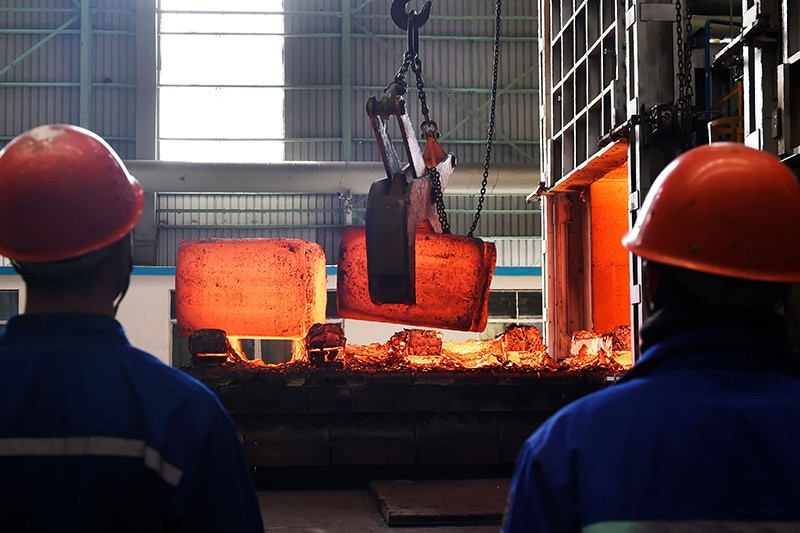 Chinese employees watch hot red steel at a steel plant in Zouping in China's eastern Shandong province on March 5, 2018. (AFP Photo)