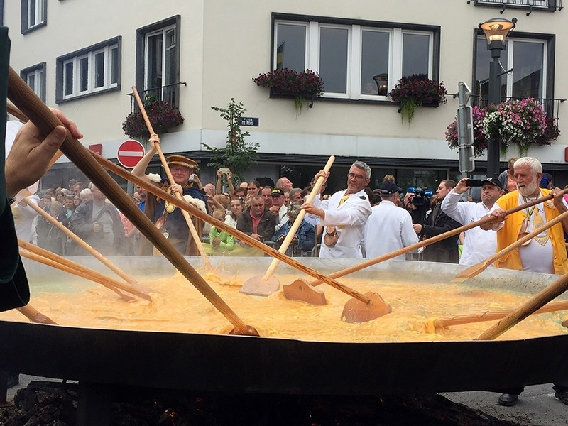 Cooks and volunteers stir eggs on an oversize pan at the 22nd Giant Omelet event in Malmedy, Belgium, Tuesday, Aug. 15, 2017 (AP Photo)