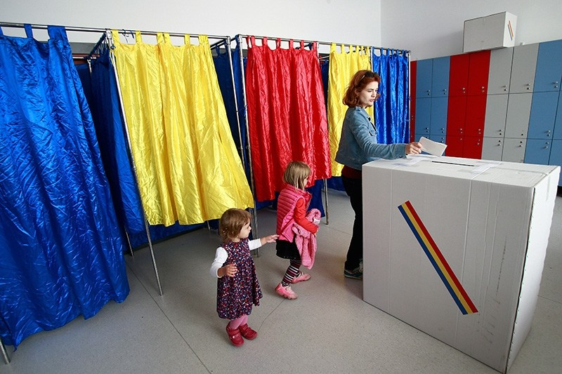 A woman is followed by her daughters while casting her ballot during the family re-definition referendum at a polling station in Bucharest, Romania, Oct. 7, 2018. (EPA Photo)