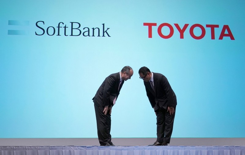 Softbank Group Corp. Chairman Masayoshi Son, left, and Akio Toyoda, right, President of Toyota Motor Corporation bow during a photo session of a joint press conference in Tokyo Thursday, Oct. 4, 2018. (AP Photo)