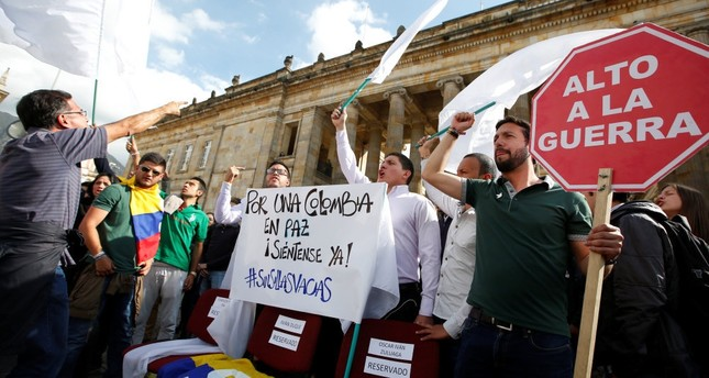 University students and supporters of the peace deal signed between the government and Revolutionary Armed Forces of Colombia (FARC) guerillas protest during a rally in front of Congress in Bogota. The sign reads: For Colombia Peace, sit here.