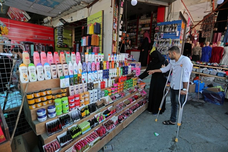 32-year-old Palestinian Mohammad Al-Ahres, who lost his left leg by Israeli fire during Gaza border protests after spending seven years in Israeli prisons, is shopping with his fiancee in Gaza, June 15, 2018. (AA Photo)