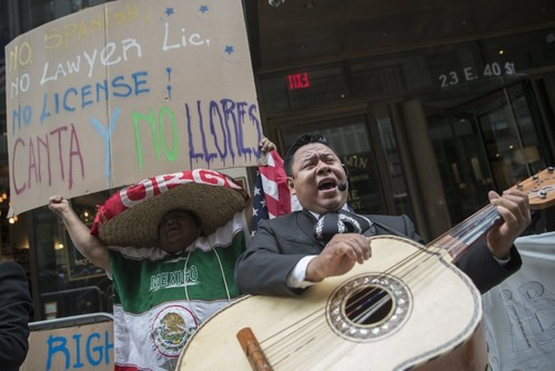 A demonstrator dances and sings along the Mariachi Tapatio de Alvaro Paulino band as they perform during a demonstration across the street from the building that once housed the office space of Aaron Schlossberg, May 18, 2018, in New York. (AP Photo)