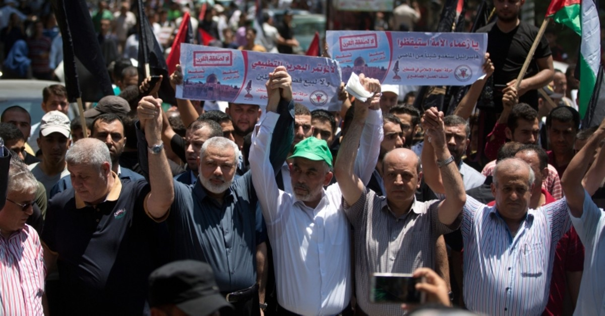 Ismail Haniyeh, third from left, and Hamas leader in the Gaza Strip Yahya Sinwar raise their hands up with leaders of the other Palestinian factions as they attend a protest against the conference in Bahrain, (AP Photo)