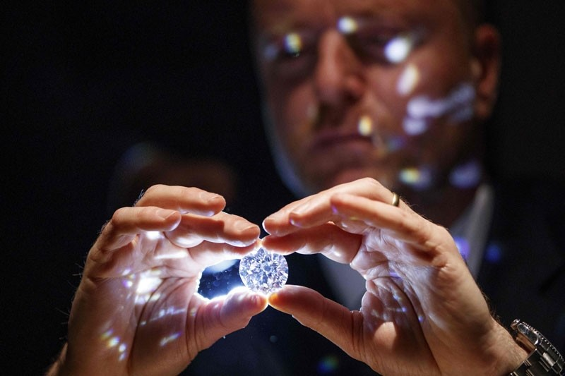 A gallery assistant poses with a 102.34 carat flawless white diamond at Sotheby's in central London on February 8, 2018.  (AFP Photo)