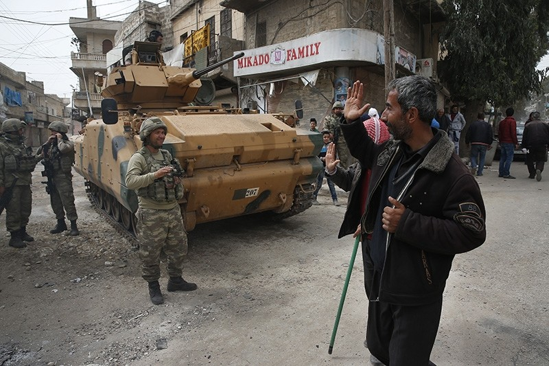 A Syrian man waves to Turkish soldiers securing the streets of the northwestern city of Afrin, Syria (AP Photo)