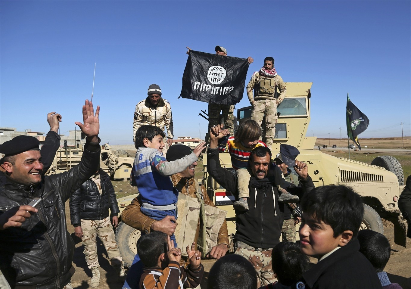 In this Jan. 24, 2017 file photo, Iraqi Army soldiers celebrate with residents of liberated neighborhoods as they hold upside down a banner of Daesh (AP Photo)