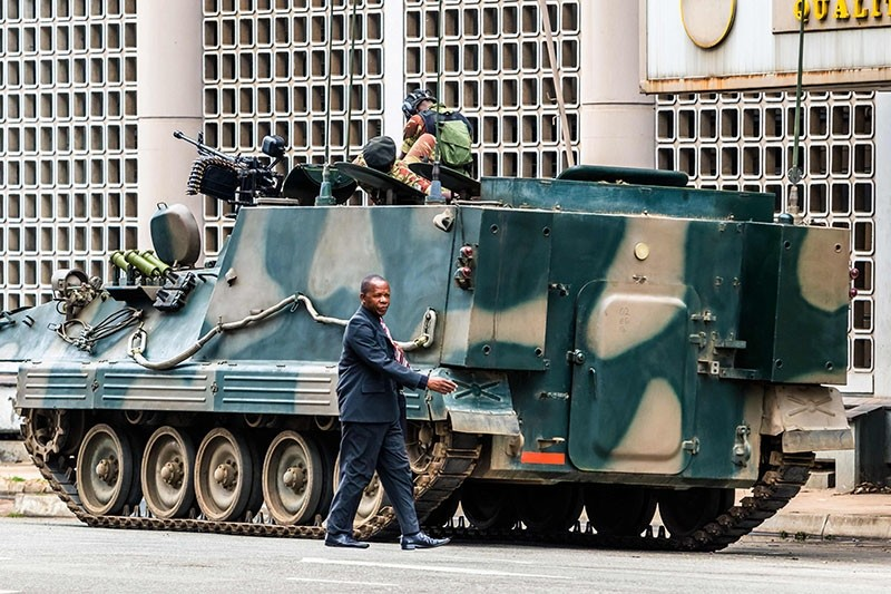 A man walks past a military tank parked on the side of a street in the Zimbabwean capital Harare on November 16, 2017 (AFP Photo)