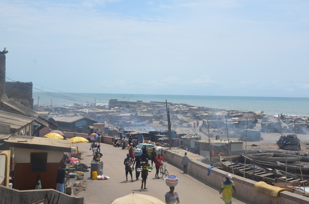 Locals walk along a coastal street in Ghana's capital city of Accra, Oct. 11.