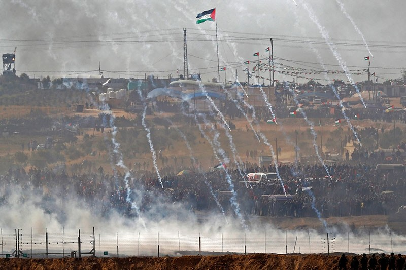 A picture taken on April 13, 2018 from the southern Israeli kibbutz of Nahal Oz across the border with Gaza Strip shows tear gas canisters launched by Israeli forces falling down on Palestinian protestors gathering along the border fence. (AFP Photo)