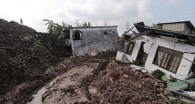 A Sri Lankan man tries to reach to a row of houses buried by a collapse of a garbage dump in Meetotamulla, on the outskirts of Colombo, Sri Lanka, Saturday, April 15, 2017. (AP Photo)