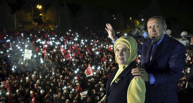 """President Recep Tayyip Erdoğan and his wife Emine Erdoğan posing for photos with cheering supporters in the background after unofficial referendum results resulted in the """"yes"""" vote's victroy, Istanbul, April 16."""