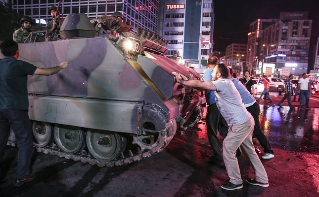 People try to stop a tank dispatched by putschists in Ankara's Kızılay Square on July 15, 2016. Ali Kalyoncu, one of the fugitives, is accused of dispatching tanks  to Ankara's streets against anti-coup civilians.