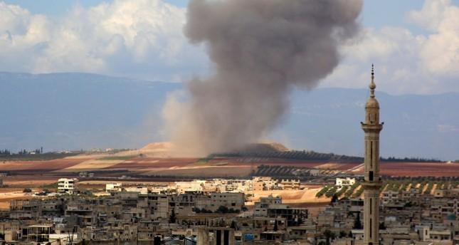 تصاعد أعمدة الدخان إثر قصف طائرة روسية على قرية كفر عين في الريف الجنوبي لإدلب (وكالة الأنباء الفرنسية)