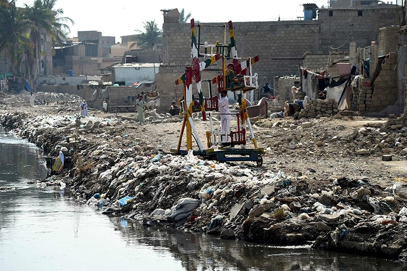 In this photograph taken on January 24, 2017, Pakistani children ride on swings alongside dumped garbage in Karachi. (AFP Photo)