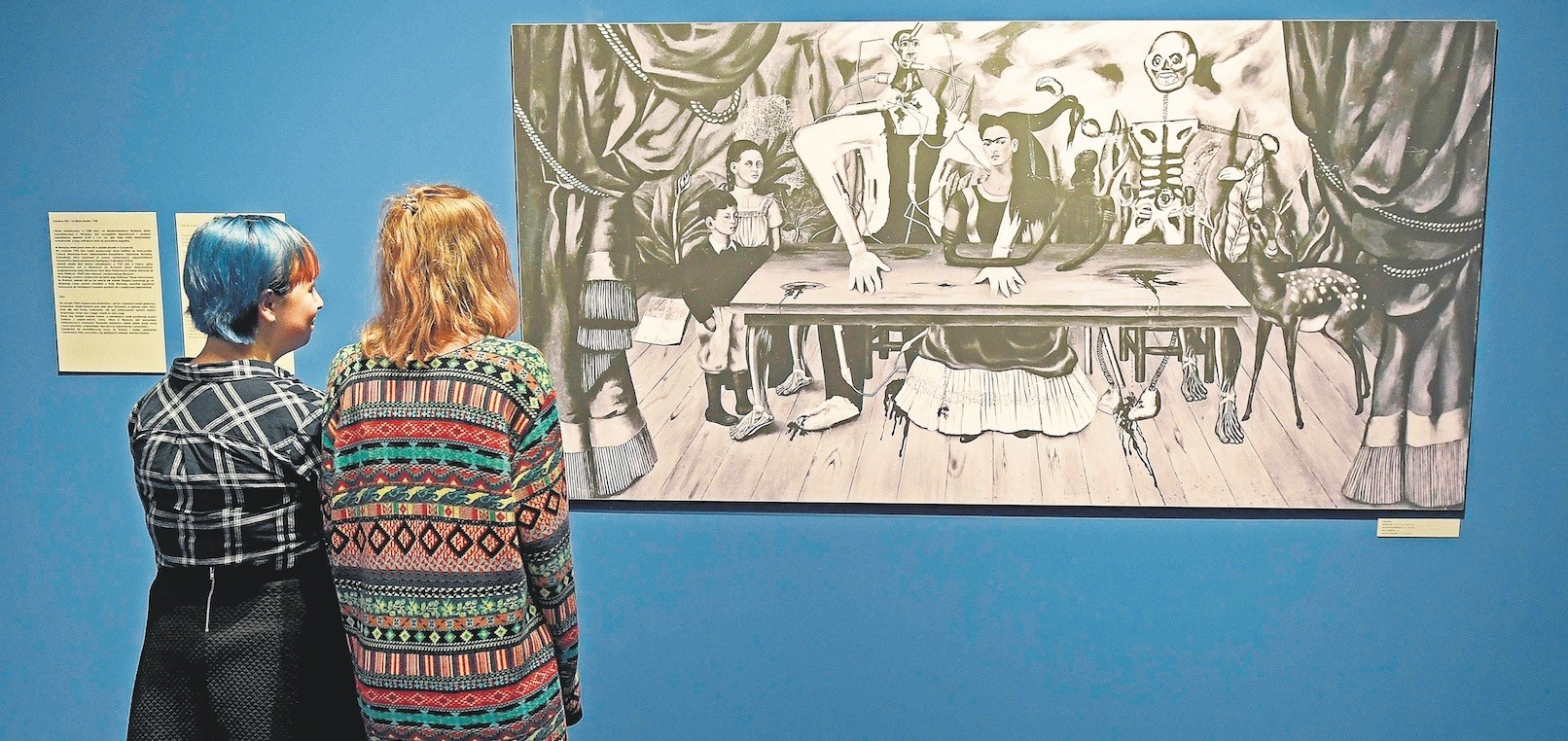 Visitors look at a black-and-white reproduction of a painting titled ,The Wounded Table, by late Mexican artist Frida Kahlo.