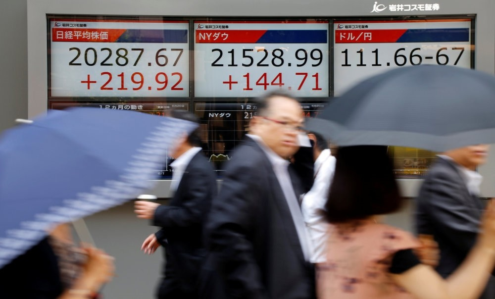 An electronic board showing Japan's Nikkei average (L), the Dow Jones average (C) and the exchange rates between the Japanese yen and dollar outside a brokerage in Tokyo.