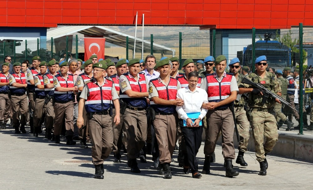 Kemal Batmaz, an executive of a FETu00d6-linked company accused of arranging the coup attempt, leads the defendants, mostly high-ranking officers, as gendarmerie troops escort them to court in Ankara.