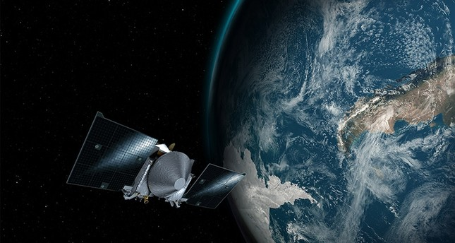 This illustration provided by NASA depicts the OSIRIS-REx spacecraft and the Earth. On Friday, Sept. 22, 2017, the probe will use Earth's gravity to put it on a path toward the asteroid Bennu. (AP Photo)
