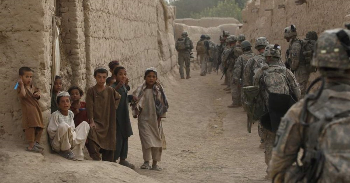Local boys watch as soldiers with the US Army's 1-320 Field Artillery Regiment, 101st Airborne Division conduct a morning patrol in the village of Saidon Kalacheh, Kandahar, July 28, 2010. (REUTERS Photo)