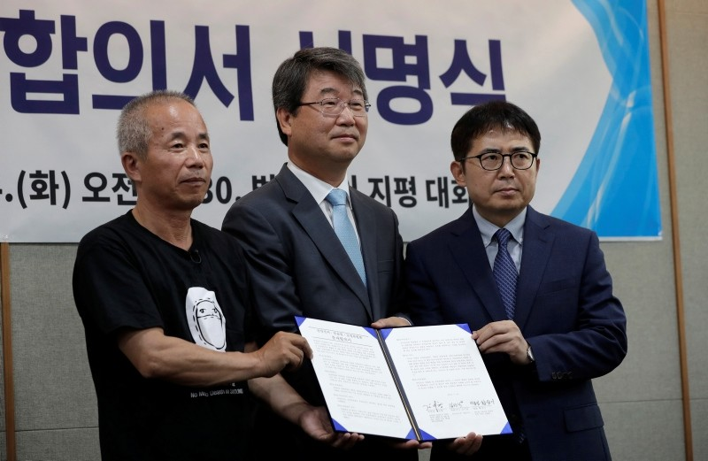 Hwang Sang-gi, father of former Samsung semiconductor who died from leukemia in 2007, Mediation Committee chairman Kim Ji-hyung and Saumsung Electronics Senior Vice President Kim Sunsig pose for the media in Seoul on July 24, 2018. (AP Photo)