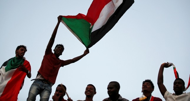 Sudanese protesters wave national flags and shout slogans as they gather for a mass protest in front of the Defence Ministry in Khartoum, Sudan, April 21, 2019. (Reuters Photo)