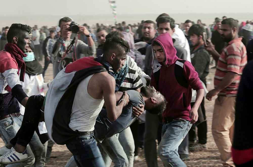 Palestinian protesters evacuate a young protester wounded by Israeli troops along Gaza's border with Israel, Friday, April 13, 2018. (AP Photo)