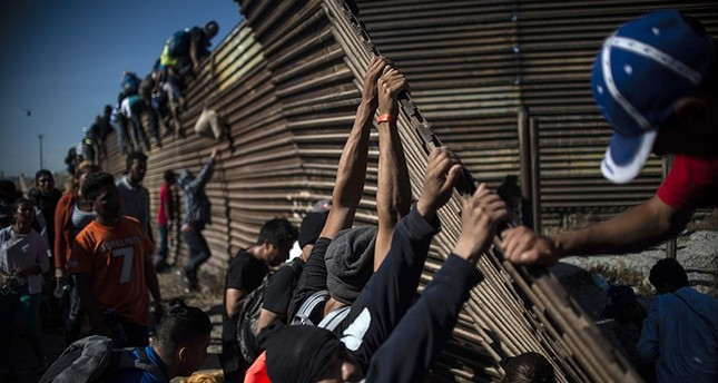 Group of Central American migrants, mostly Honduran,  climb border fence between Mexico and United States as others try to bring it down, near El Chaparral border crossing, in Tijuana, Baja California State, Mexico, Nov. 25, 2018. (AFP Photo)