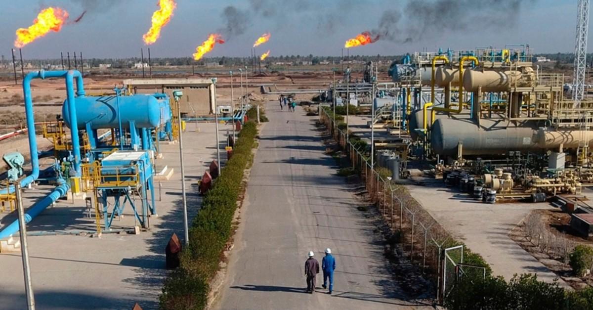in this Thursday, Jan. 12, 2017 file photo, laborers walk in the Nihran Bin Omar field north near Basra, Iraq. (AP Photo)