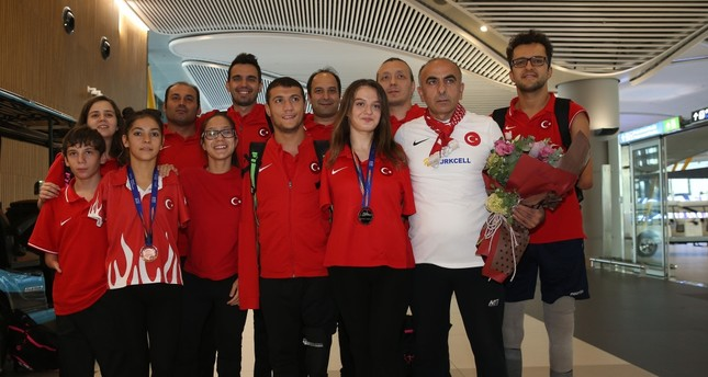 Sümeyye Boyacı, third from  right, and Sevilay Öztürk, third from left, pose with their medals at Istanbul Airport after they returned from London, Sept. 16, 2019.