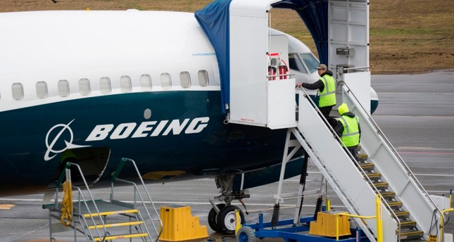 In this file photo taken on March 12, 2019 workers are pictured next to a Boeing 737 MAX 9 airplane on the tarmac at the Boeing Renton Factory in Renton, Washington. (Reuters Photo)