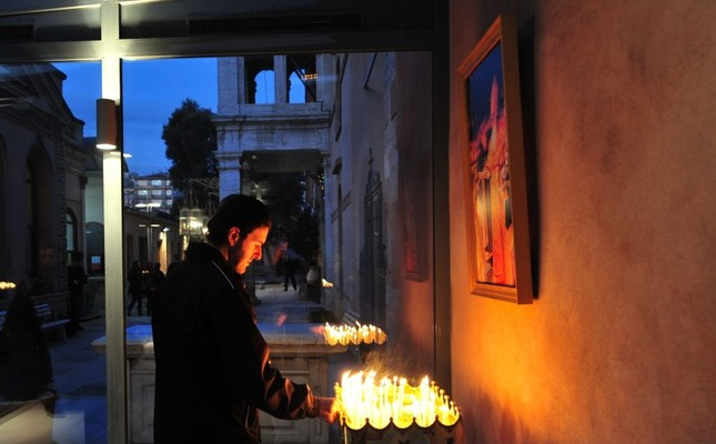 A man lights a candle outside Vorots Vorodman, a restored Armenian church in Istanbul. In the past decade, the state sped up restoration of derelict churches.