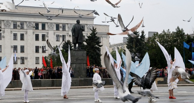 People take part in Victory Day celebrations to mark the defeat of Nazi Germany in World War II, as pigeons fly above in the rebel-controlled city of Luhansk, Ukraine, May 9, 2019.