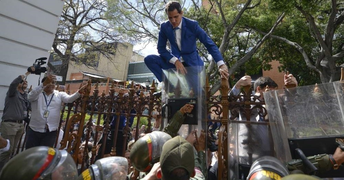 National Assembly President Juan Guaido, Venezuela's opposition leader, climbs the fence in a failed attempt to enter the compound of the Assembly, as he and other opposition lawmakers are blocked from entering a session to elect new Assembly leadership in Caracas, Venezuela, Sunday, Jan. 5, 2020. (AP Photo/Matias Delacroix)