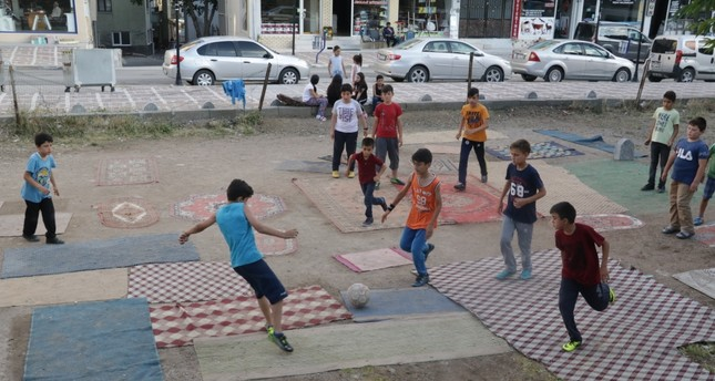 Children play football on carpets and rugs they laid down on an empty lot, June 26, 2019.
