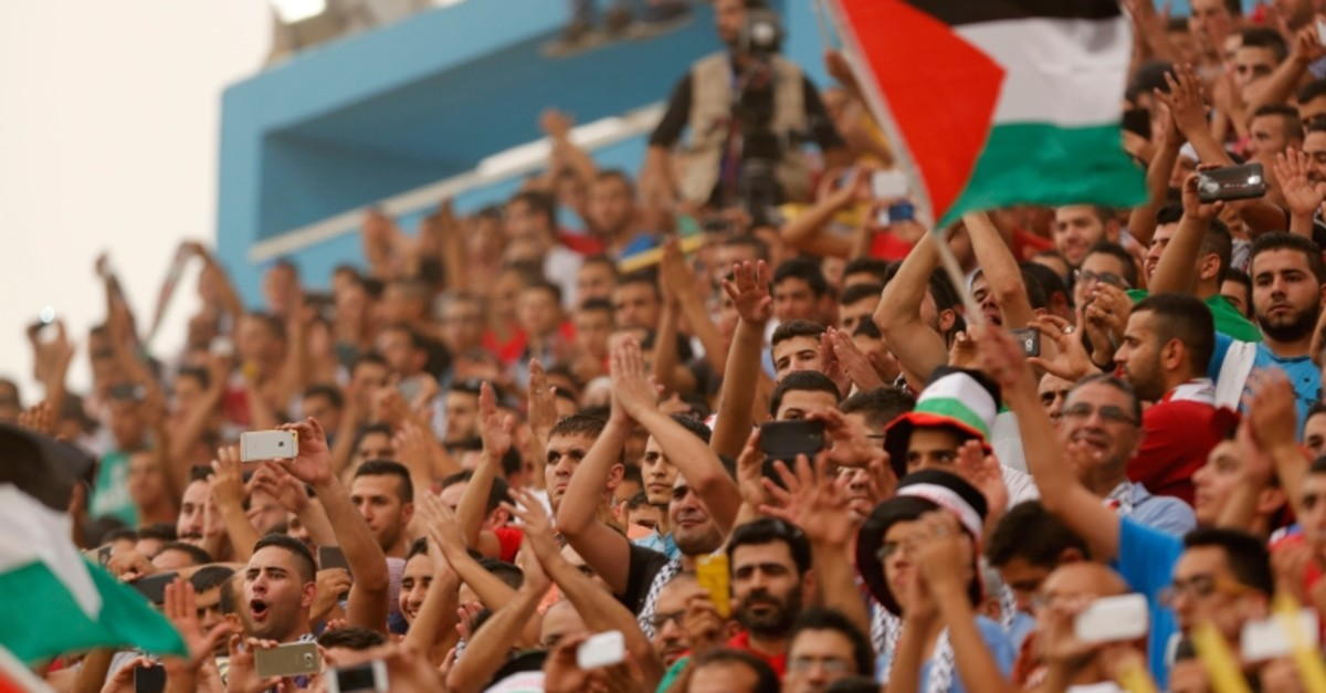 In this Sept. 8, 2015 file photo, Palestinian fans cheer during a World Cup soccer qualifying match between the Palestinian and the UAE teams at the Faisal al-Husseini stadium in the West Bank town of Al-Ram. (AP Photo)