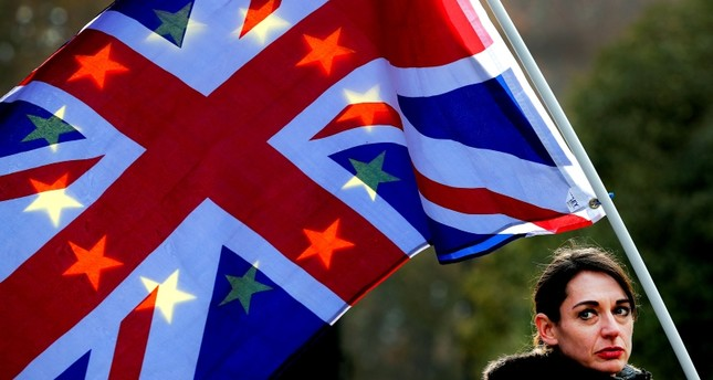 A protester holds flags against the sunlight at a demonstration against Brexit opposite the House of Parliament in London, Tuesday, Nov. 27, 2018. (AP Photo)