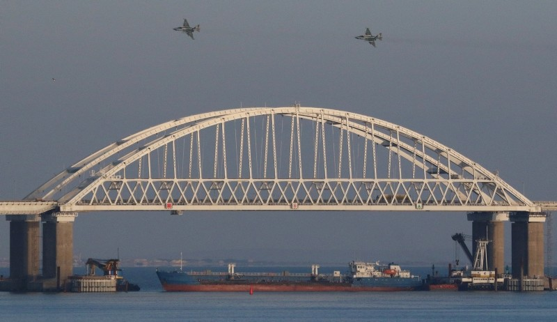 Russian jet fighters fly over a bridge connecting the Russian mainland with Crimea with a cargo ship beneath it after three Ukrainian navy vessels were stopped by Russia from entering the Azov Sea via the Kerch Strait, Nov. 25, 2018. (Reuters Photo)