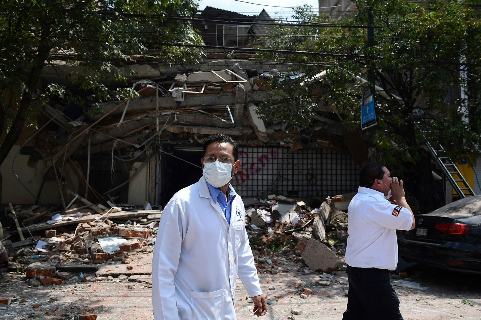 Medical staff walk by a building which collapsed during a quake in Mexico City on September 19, 2017. (AFP Photo)