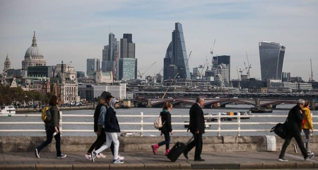 In this file photo, pedestrians walk with the London skyline in the background, Oct. 27, 2016. AFP Photo