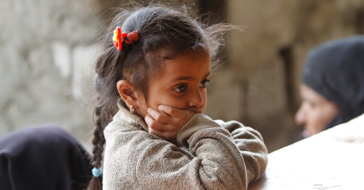 A girl waits for a meal at a charity kitchen, Sanaa, May 10, 2019.