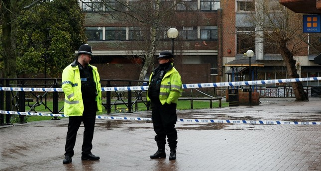 Police officers stand at cordon tape close to where former Russian intelligence officer Sergei Skripal and his daughter Yulia were found poisoned, Salisbury, Britain, March 28.