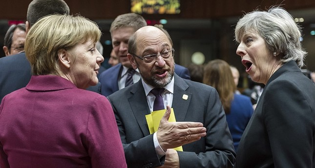 German Chancellor Angela Merkel, left, speaks with British Prime Minister Theresa May, right, and European Parliament President Martin Schulz, center, durıng a round table meetıng at an EU summit in Brussels on Thursday, Dec. 15, 2016. (AP Photo)