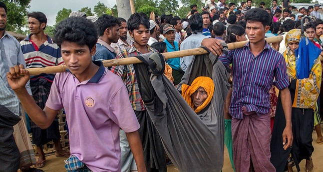Rohingya Muslim men, who crossed over from Myanmar into Bangladesh, carry their mother in a cloth tied to bamboo stick at Kutupalong refugee camp, Bangladesh, Monday, Oct. 23, 2017 (AP Photo)