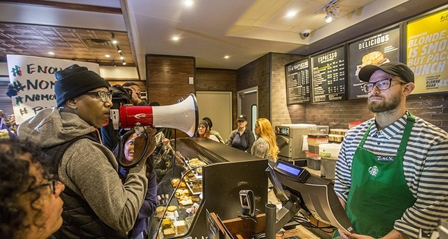 Local Black Lives Matter activist Asa Khalif, left, stands inside a Starbucks, Sunday April 15, 2018, demanding the firing of the manager who called police resulting the arrest of two black men on Thursday (AP Photo)