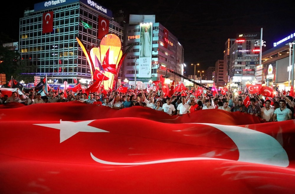 People hold a large Turkish flag during a march to mark the first anniversary of the coup attempt, Ankara, July 15.