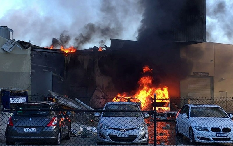 This frame grab taken from AFPTV of video received from Jordan Fouracre on February 21, 2017 shows smoke and flames after a twin-engined Beechcraft plane crashed into a shopping center just after take-off from an airport near Melbourne. (AFP Photo)