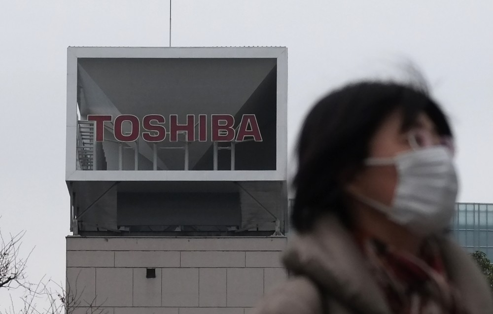 A woman walks in front of the logo of Japanese corportation Toshiba in Tokyo.